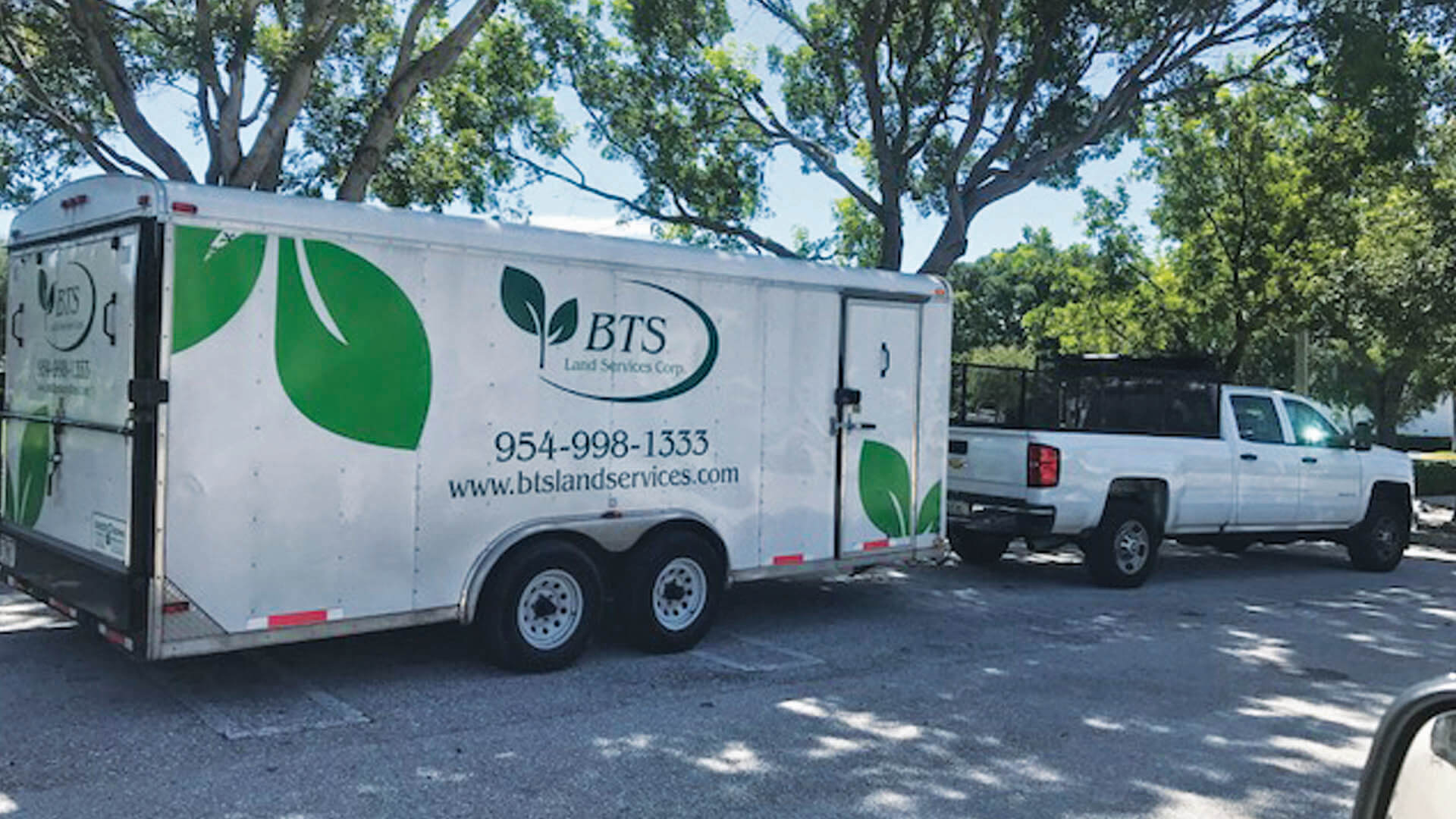 BTS Land Services Corp truck and trailer for commercial lawn and landscaping services.